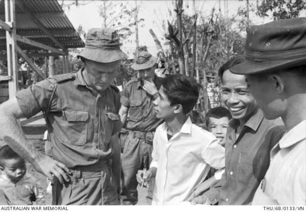 3 Troop Commander CAPT Viv Morgan, speaks with a Vietnamese interpreter, while other villagers watch on, at Trang Bom village, about replacing the many houses destroyed in the Viet Cong attack.