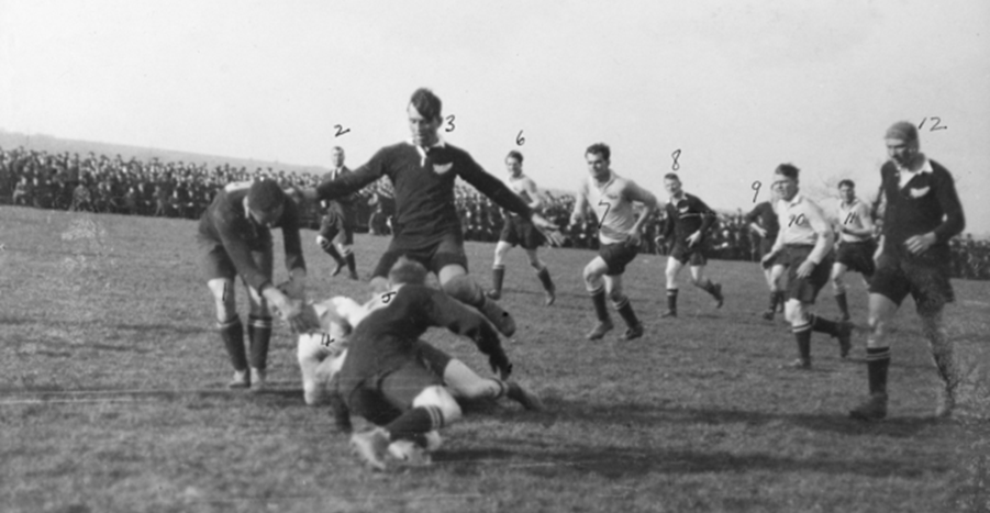Fullback Captain Bruce 'Jackie' Beith is tackled in the match between Australia and New Zealand and at Bradford, England on 9 April 1919. Identified: 1. A. Wilson, New Zealand (NZ); 2. Referee Mr Yeadon; 3. Private A. Singe, NZ forward; 4. Captain Bruce 'Jackie' Beith; 5. unidentified NZ forward; 6. Sergeant Joseph Murray; 7. Corporal Vivian 'Viv' Dunn; 8. R. Sellars, NZ; 9. unidentified NZ, obscured; 10. Lieutenant Horace 'Dick' Pountney; 11. Lieutenant Ernest 'Bill' Cody; 12. Ernest Belliss, NZ. (AWM D00535K)