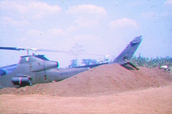 HUEY COBRA AT ANDERSEN WITH ITS TAIL ROTOR KNOCKED OFF BY AN EMPTY PLASTIC DRUM BLOWING ABOUT IN THE MAIN ROTOR WASH Photo: Sapper Brian Hopkins 3 Troop