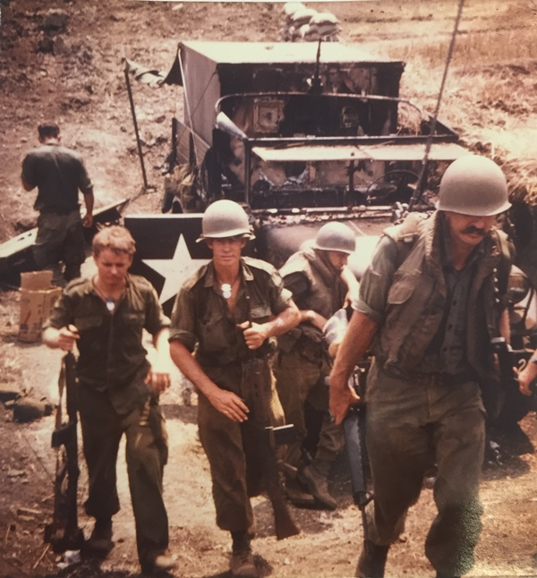 BURNT OUT US ARMY TRUCK HIT BY MORTARS DURING 1st ENEMY ASSAULT. L to R CPL Merv Dodd (back to camera) Standing Patrol survivor SPR Murray Walker and SPR Vic Underwood, with (in flak jackets) two US Army Field Artillery Gunners. Photo: Sapper Peter Macdonald 3 Troop