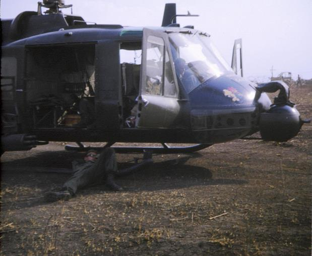 FSB ANDERSEN 19 February 1968. AN AMERICAN HUEY GUNSHIP PILOT TAKES A NAP IN THE SHADE OF HIS MACHINE, ANOTHER PILOT INSIDE Photo: Sapper Peter Macdonald 3 Troop