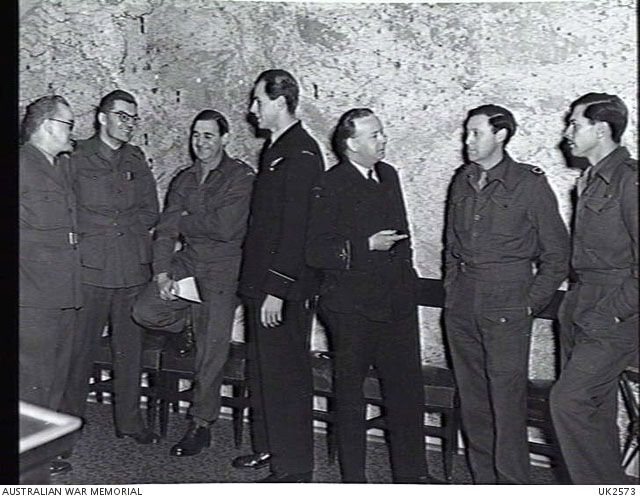 Paris, France. 18 February 1945. A group of Australian war correspondents. Left to right: Colin Bingham, of Sydney Morning Herald; Henry Bateson of Truth and Sydney Daily Mirror; King Watson, of Sydney Daily and Sunday Telegraph; Flying Officer (FO) J. Flower, RAAF Public Relations Officer (PRO); FO J. Toohey, RAAF PRO; Godfrey Blunden, of Sydney Daily and Sunday Telegraph; Geoffrey Hutton, of Melbourne Argus. The map on the wall is kept for background for photos taken in the briefing room.